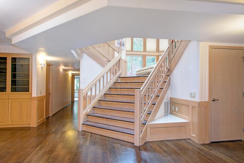 White wooden hallway interior accented with a beautiful staircase. Polished hardwood floor, taupe striped wallpaper paired with board and batten walls framing stock photo