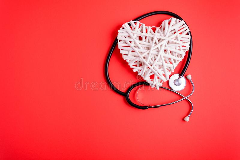 White wooden heart with black stethoscope on red paper background. Heart health concept. stock photography