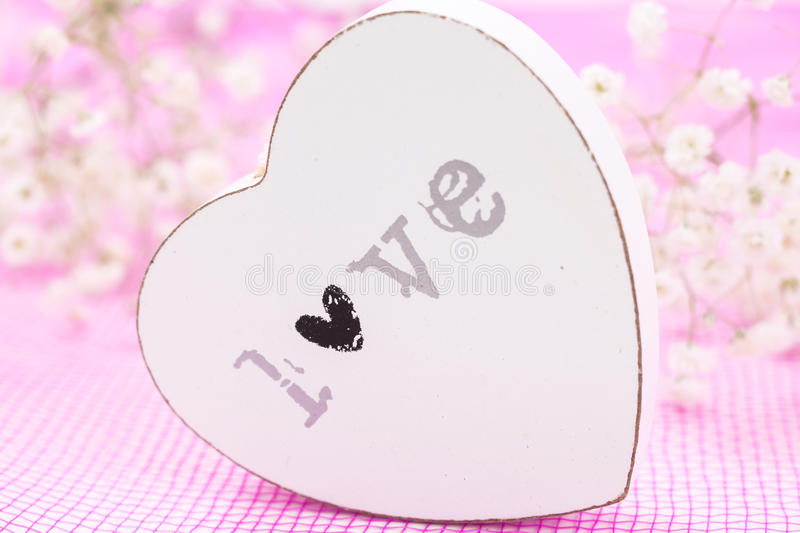 White wooden heart closeup with word Love, on pink mesh fabric and white flowers stock photo