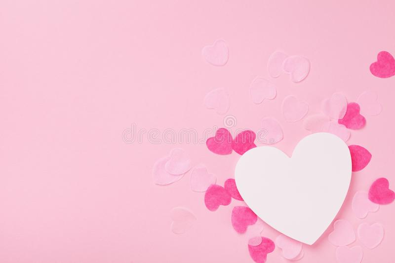 White wooden heart and paper hearts on pink pastel background top view. Greeting card for Valentines, Woman or Mothers Day. stock photography