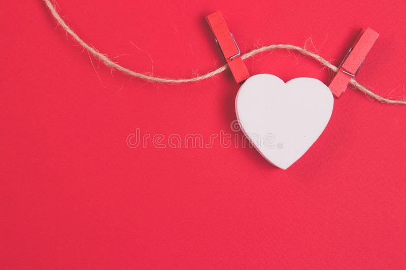 White wooden heart on a thread with red clothespins on a red background. Banner for you design royalty free stock photos