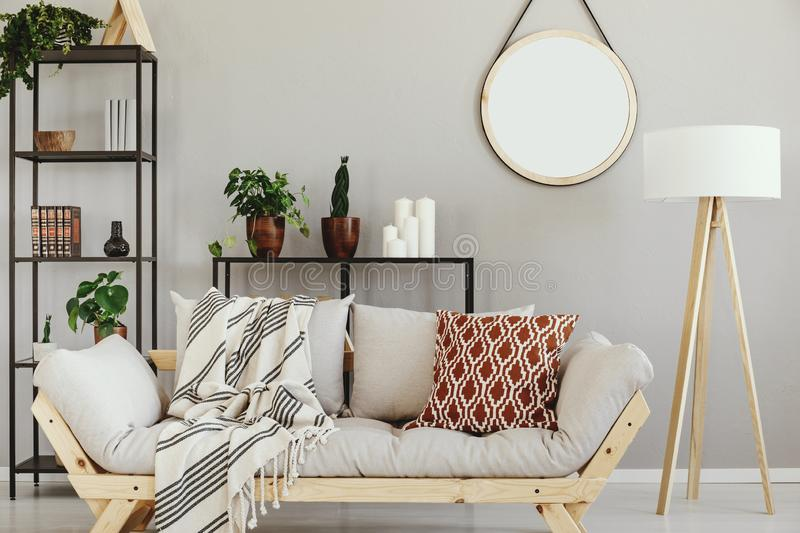 White wooden lamp next to stylish scandinavian couch with patterned pillow in elegant living room interior. White wooden lamp next to stylish scandinavian couch stock photos