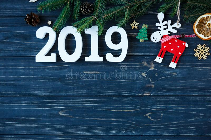 White wooden numbers 2019 with decor, branches of spruce on the gray wooden table. New year and Christmas decoration concept stock photo