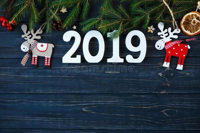 White wooden numbers 2019 with decor, branches of spruce on the gray wooden table. New year and Christmas decoration concept royalty free stock images