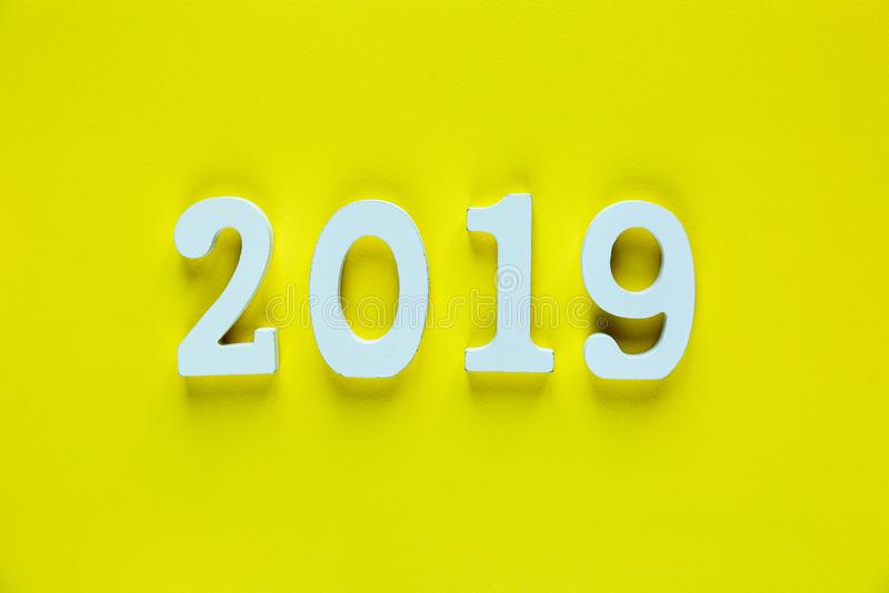 White wooden Numbers 2019 on yellow background. cr. Eative Christmas and New year background, decoration, postcard concept royalty free stock image