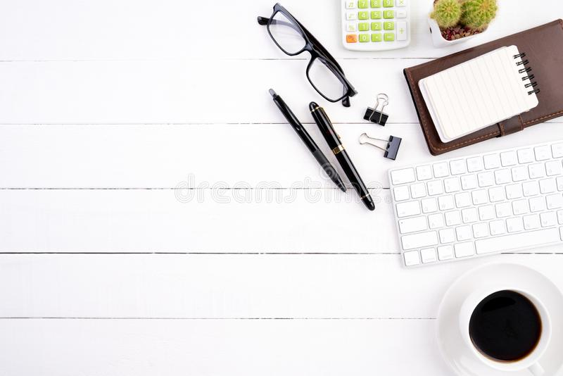 White wooden office desk table with blank notebook, computer keyboard calculator, coffee cup and other office supplies. Top view stock photos