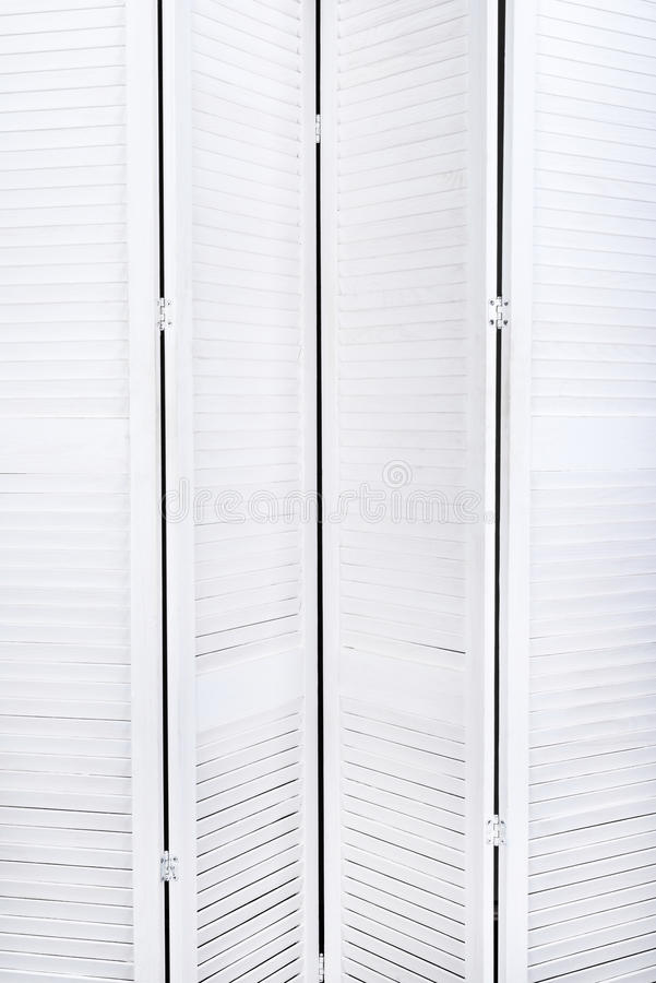 White wooden screen for changing clothes with a texture for the background. Vertical frame. White wooden screen for changing clothes with a texture for the stock images