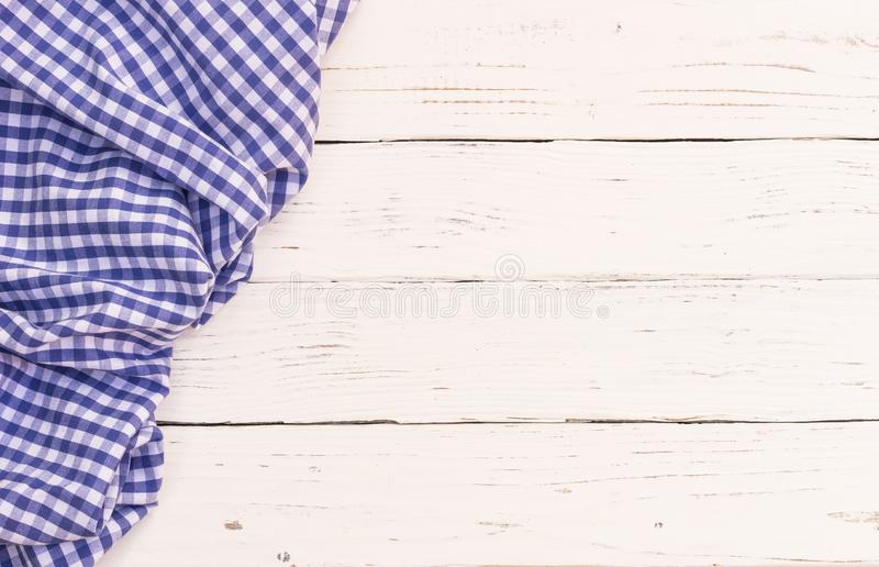 Blue checked tablecloth covered empty white wood table background. White wooden table background rustic texture, with blue checkered tablecloth, high angel view stock photos