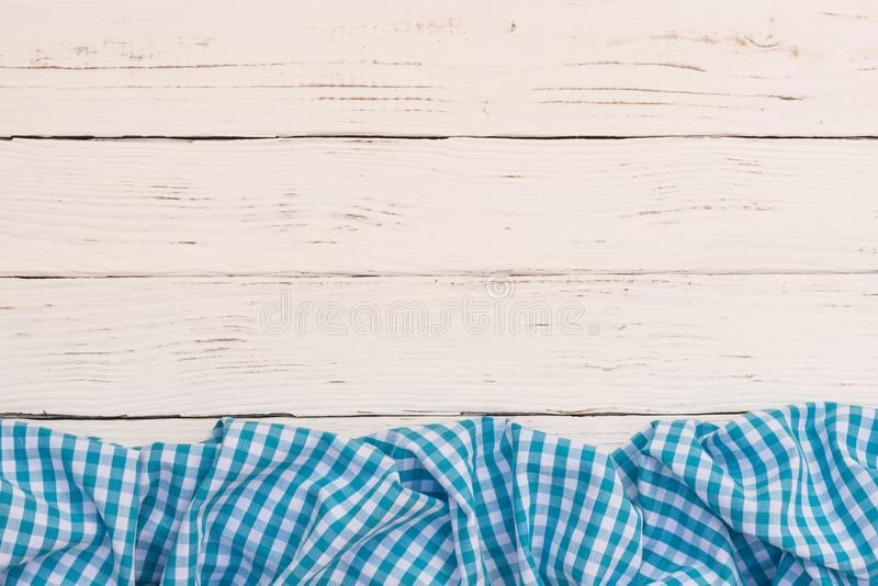 Blue rustic tablecloth border on white wood tabel background, top view, copy space. White wooden table background rustic texture, with blue checkered tablecloth stock photography