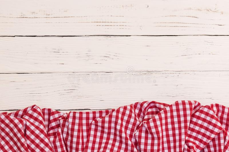 Red picnic tablecloth on rustic white wooden table background, top view, copy space. White wooden table background rustic texture, with red checkered tablecloth stock image