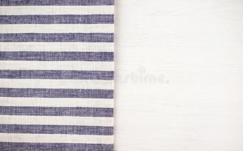 White wooden table with a blue striped tablecloth. stock image