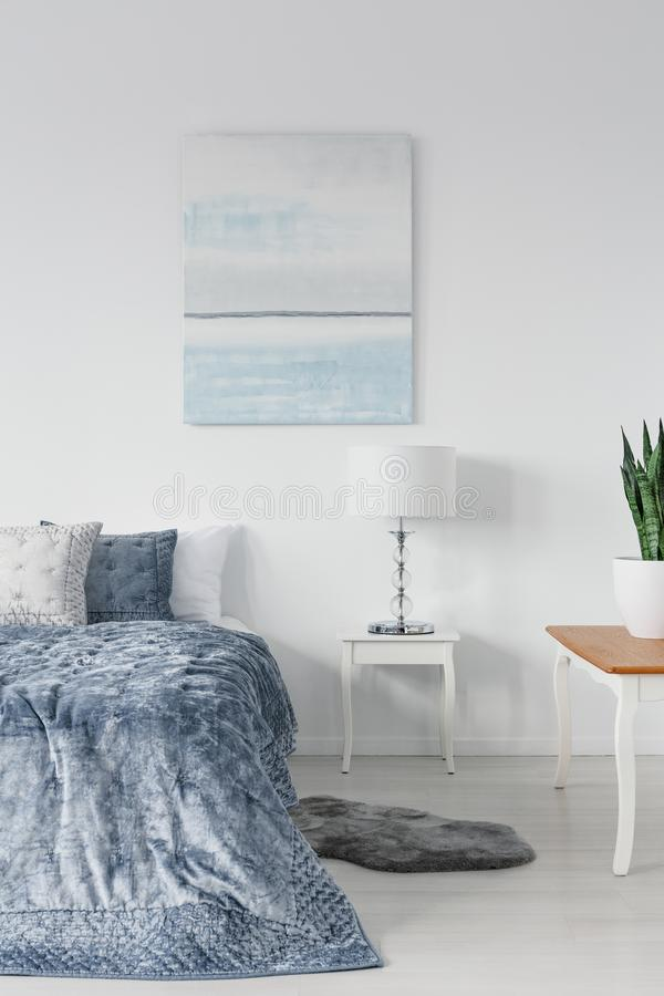 White wooden table with stylish lamp next to comfortable ned with blue pillows and duvet, real photo royalty free stock images
