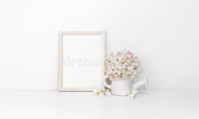 White wooden vertical frame mockup with flowers royalty free stock photo