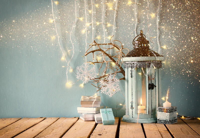 White wooden vintage lantern with burning candle, wooden deer, christmas gifts and tree branches on wooden table. retro filtered i royalty free stock image