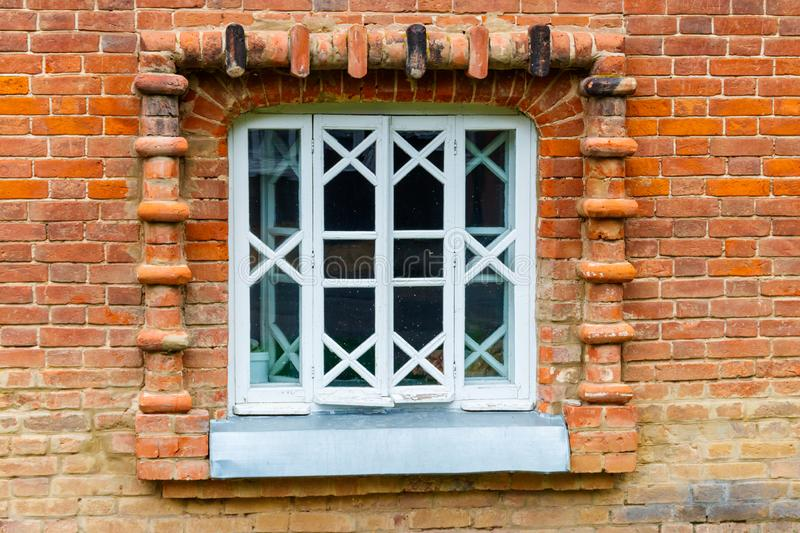 White wooden window on old red brick wall stock photo