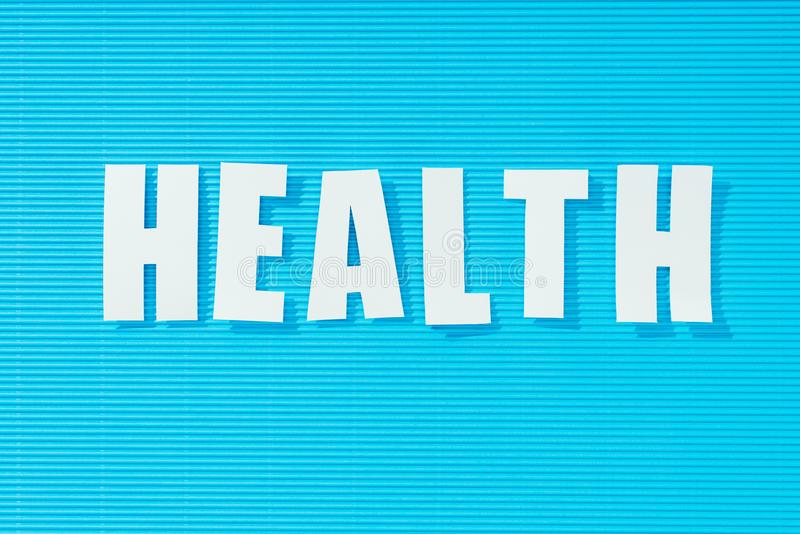 White word health on bright blue striped background,. Health concept royalty free stock image