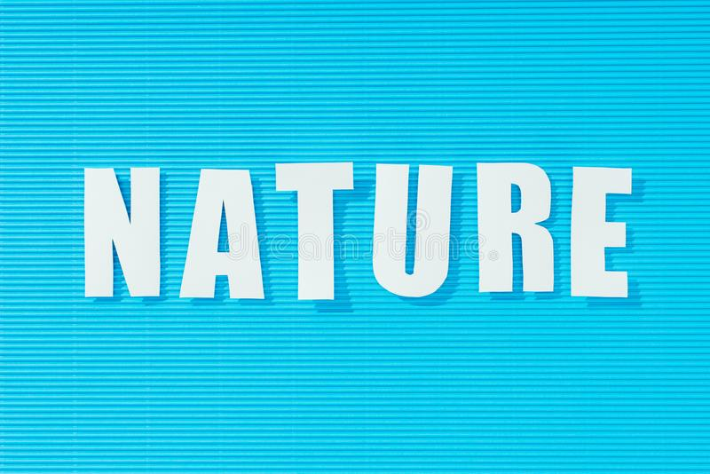 White word nature on bright blue striped background,. Nature concept stock photos