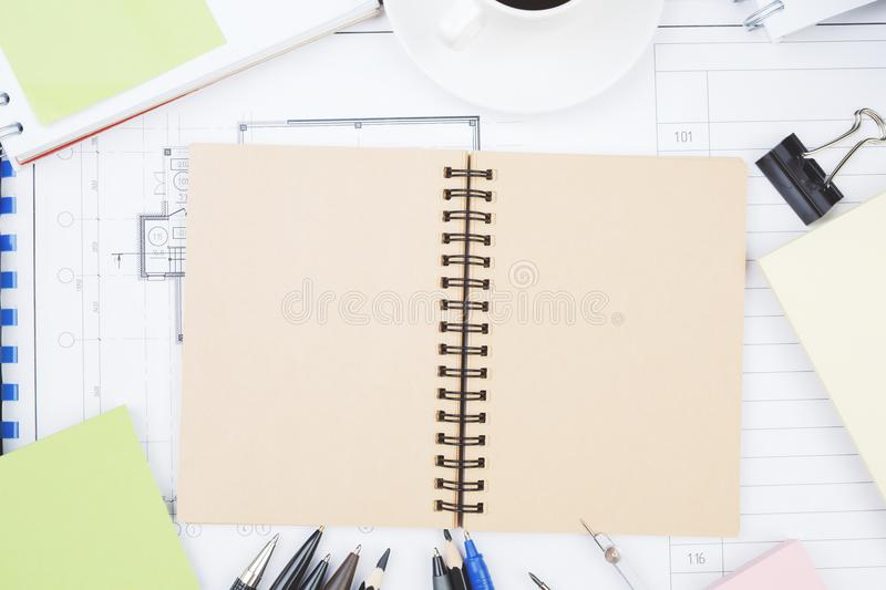 White workplace with notepad and sketch. Top view of white workplace with empty notepad, architectural project sketch and other items. Mock up. Occupation and royalty free stock photo