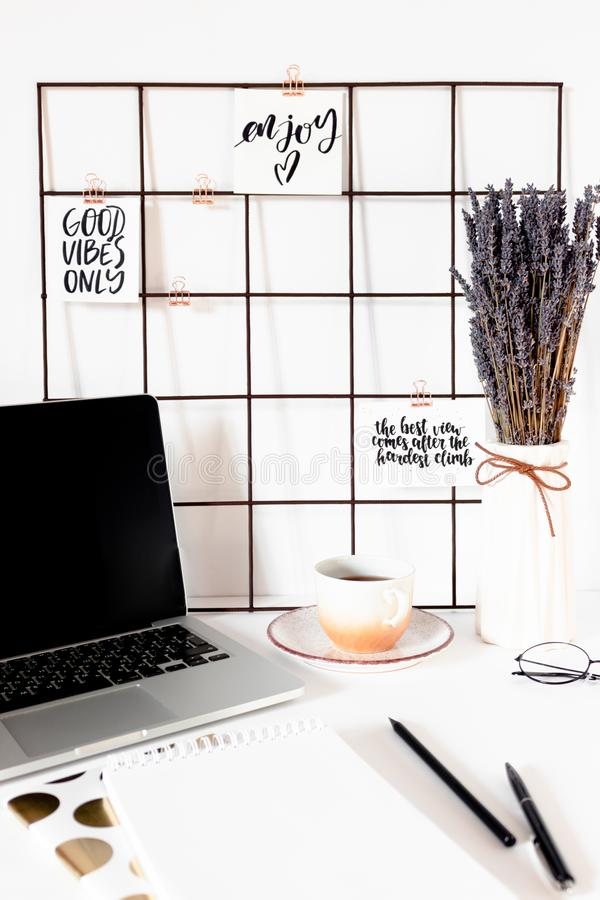 White workspace with quotes on mood board, laptop, stationery, mug of coffee royalty free stock photos