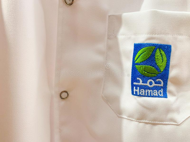 White workwear of a doctor or assistant with Hamad logo in Arabic and English. Hamad HMC is the biggest medical provider. April. 2019, Doha/ Qatar royalty free stock photo