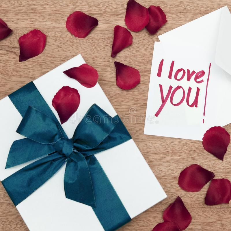White wrapped gift with a turquoise ribbon and a I-love-you-note with a white envelope on a wooden board, surrounded by red rose p stock photography