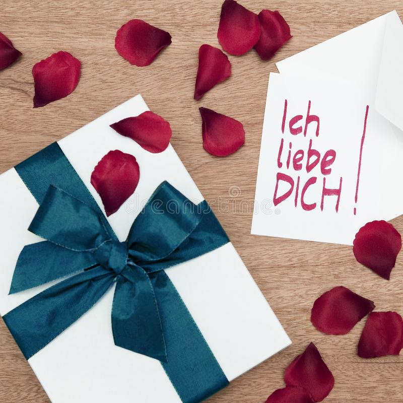 White wrapped gift with a turquoise ribbon and a I-love-you-note in German with a white envelope on a wooden board, surrounded b stock image