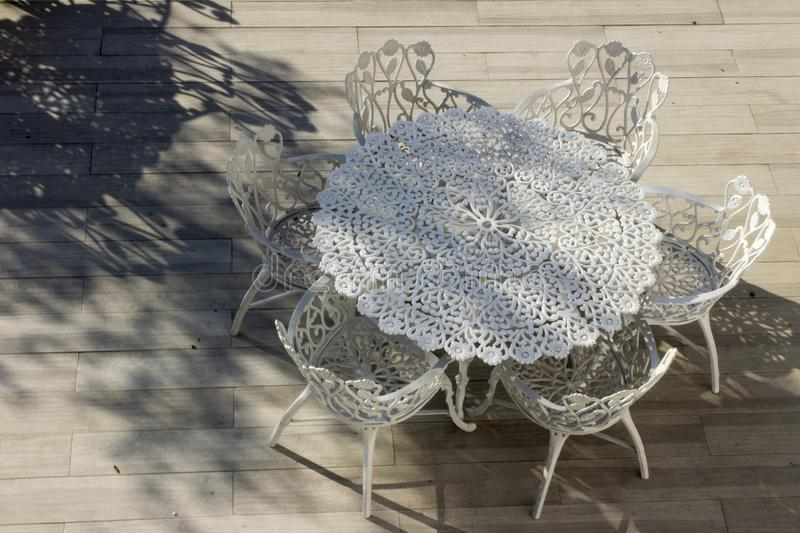 White wrought iron chairs and table stock photography