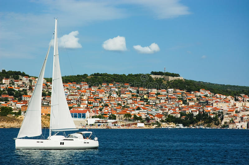 White sailing yacht in full sail on the Adriatic S. A white yacht in full sail cruises past the coastline of Croatia on a deep blue Adriatic Sea stock image