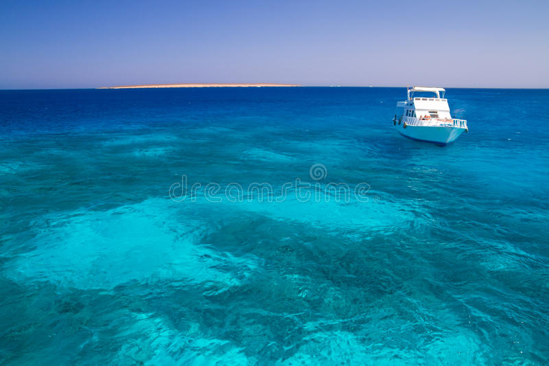 The white yacht moored beside the island Paradise. Snorkeling point tourists and motor yachts on Red Sea. Popular and famous tourists destination in Hurghada stock photography