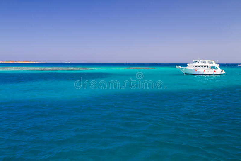 The white yacht moored beside the island Paradise. Snorkeling point tourists and motor yachts on Red Sea. Popular and famous tourists destination in Hurghada stock images