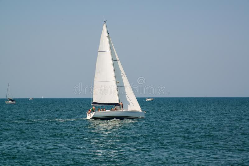 White yacht in the open azure sea near the resort of Rimini, Italy. royalty free stock images