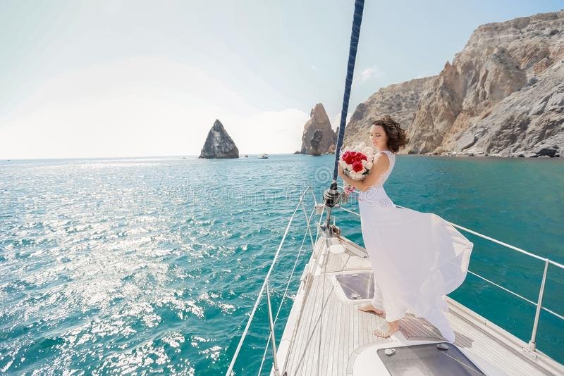 White yacht with sail set goes along the island on a hot day. blue sea, blue sky. Crimea. on board a young couple in. Love. the bride and groom. wedding boat stock image