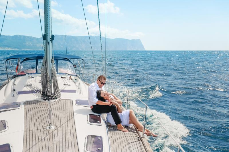 White yacht with sail set goes along the island on a hot day. blue sea, blue sky. Crimea. on board a young couple in. Love. the bride and groom. wedding boat royalty free stock image