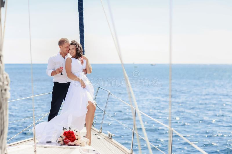 White yacht with sail set goes along the island on a hot day. blue sea, blue sky. Crimea. on board a young couple in. Love. the bride and groom. wedding boat stock photography