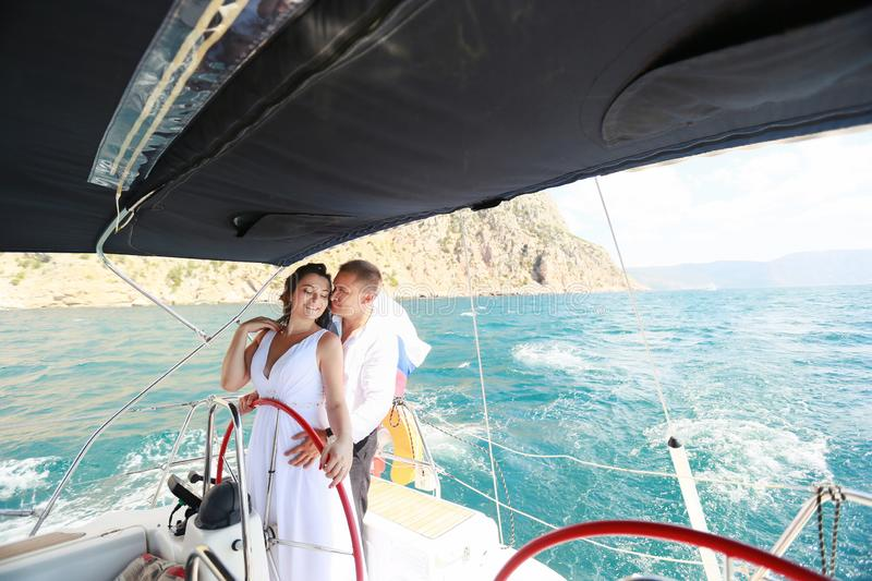 White yacht with sail set goes along the island on a hot day. blue sea, blue sky. Crimea. on board a young couple in. Love. the bride and groom. wedding boat royalty free stock photos