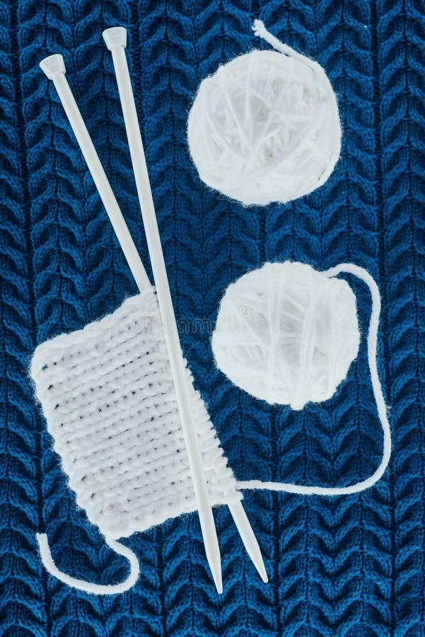 White yarn balls and knitting needles. Top view of white yarn balls and knitting needles on blue knit royalty free stock photos