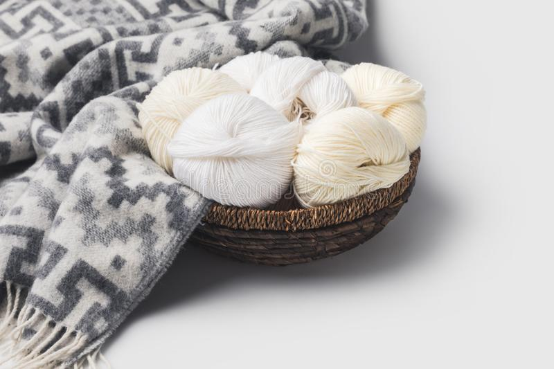 White yarn balls in wicker basket with blanket. Isolated on white royalty free stock image