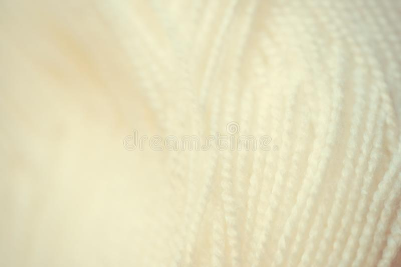 White yarn close-up shot. Woolen threads for knitting a macro. Fabric background texture. Vintage toned royalty free stock photo