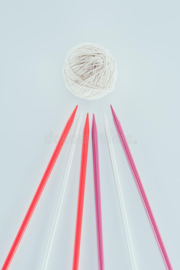 White yarn and different knitting needles isolated on white. Top view of white yarn and different knitting needles isolated on white stock photography