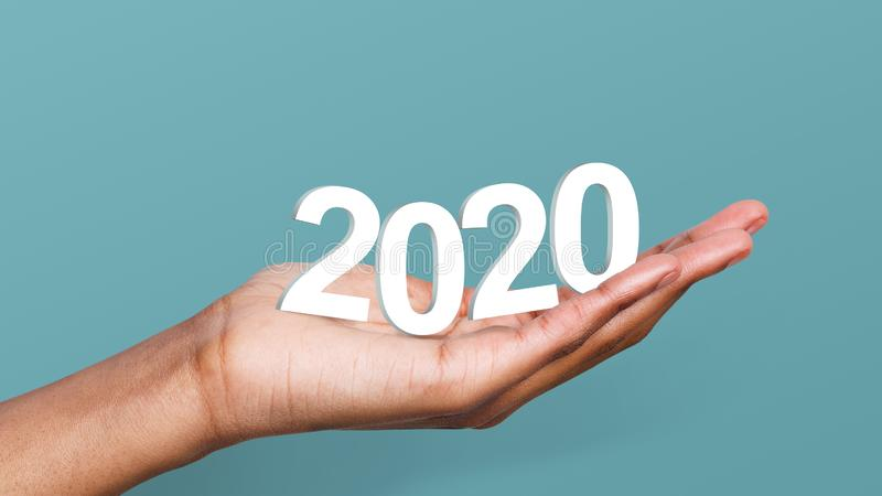 2020 year trends concept. White 2020 year numbers in woman`s hand at blue background. 2020 year trends concept stock image