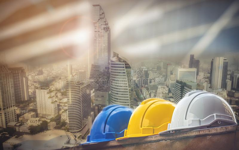 White, yellow and blue hard safety helmet hat for safety project of workman as engineer or worker, on concrete floor on city.  royalty free stock image