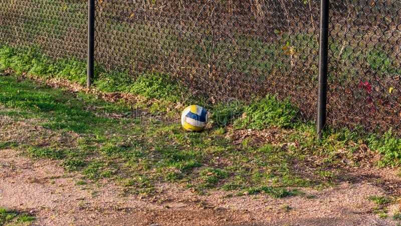 White, yellow and blue soccer ball resting on the ground at a park in the golden hour sun.  royalty free stock photography
