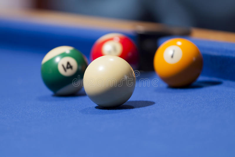 White, yellow, green and red billiard balls in a pool table. Focus on white billiard ball stock image
