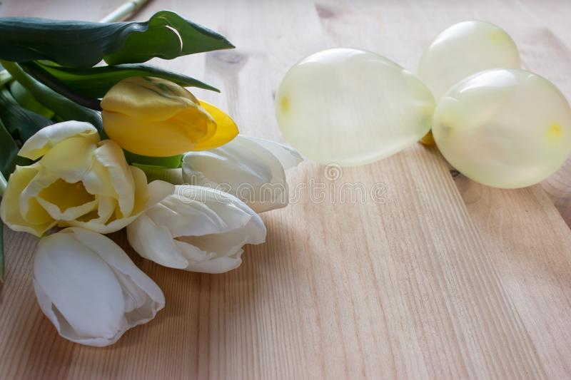 White and yellow lupans, yellow little balloons on a light wooden background stock image