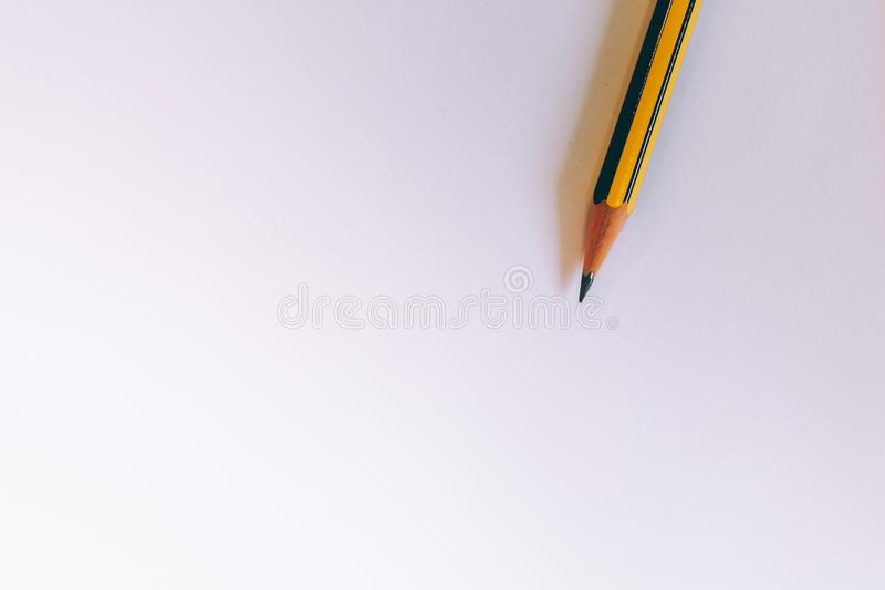 White and yellow pencil on blank piece of white paper. Office supply, creativity, education and design conept stock photos