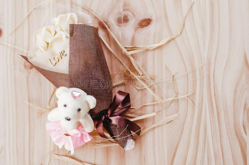 White and yellow roses flowers with valentine festival gift beautiful net bouquet and love word on the bouquet with baby bear doll royalty free stock image