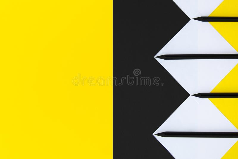 White and yellow stickers with black pencils lined with a geometric pattern on a background of black and yellow stock photography