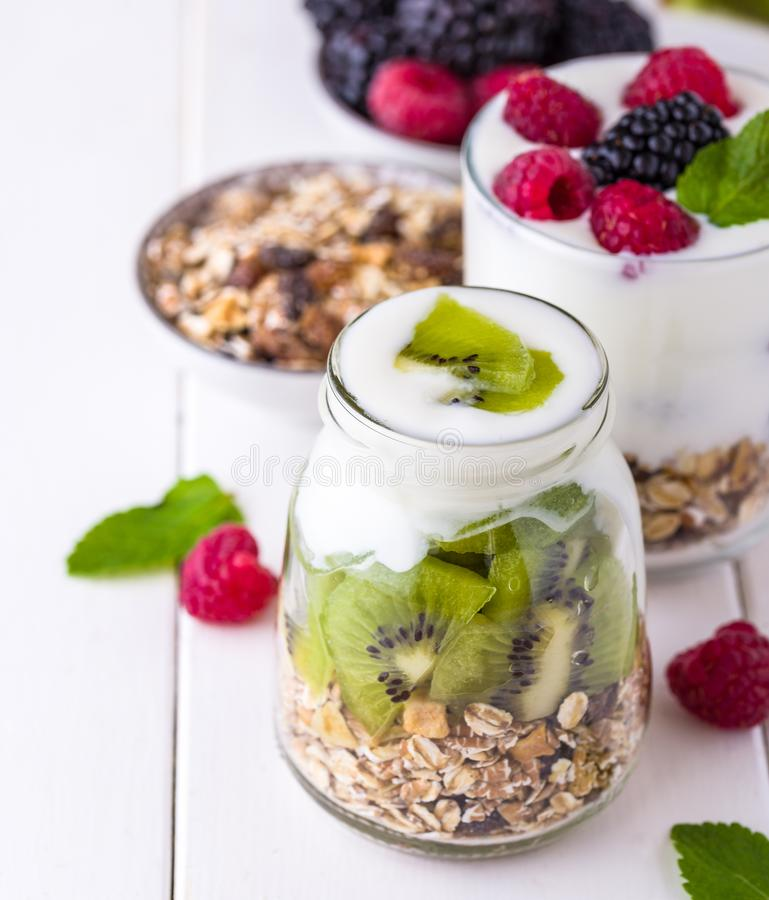 White yogurt with muesli in glass bowl with pieces of kiwi on to. P stock photography