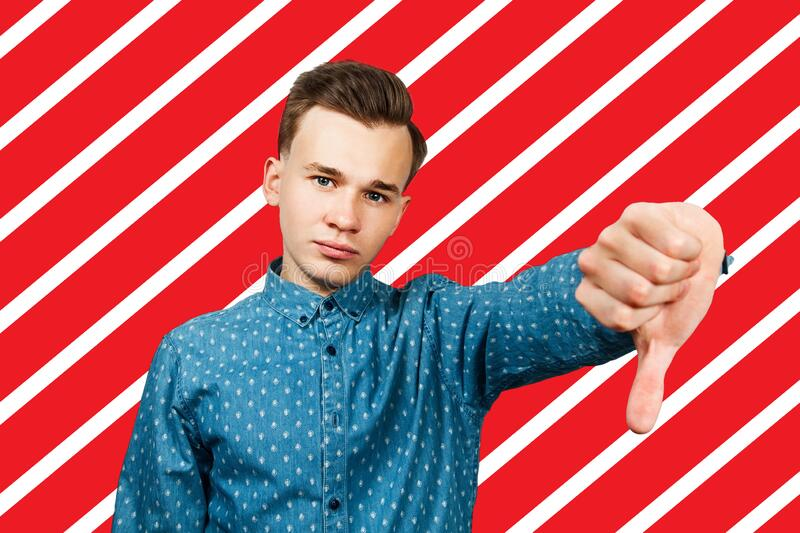 White young man showing thumb down gesture dressed in blue shirt royalty free stock photos
