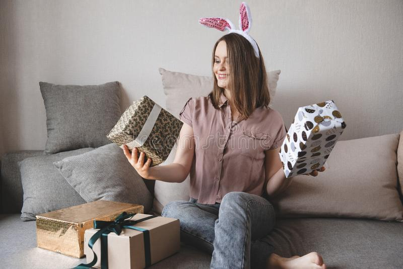 White young woman with pink rabbit ears on her head sitting on the couch with gift boxes and smiling, girl in pink blouse and stock photo